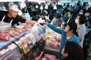 正月用の食材を買い求める人たちでにぎわう市場=30日、那覇市松尾・牧志公設市場(下地広也撮影)