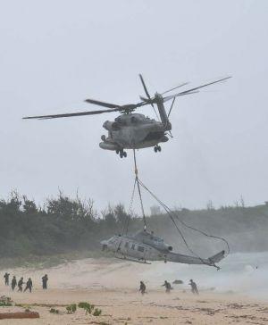 CH53につり下げられ撤去される不時着したUH1Yヘリ=8日午前10時16分、うるま市・伊計島