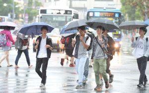 大雨の中、傘をさして歩く人たち=13日午前、那覇市久茂地