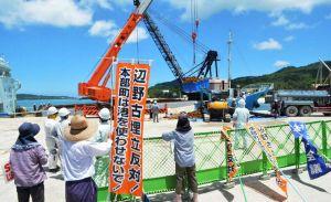 新基地建設に反対する市民が見守る中、運搬船に積み込まれる土砂=25日、本部港塩川地区