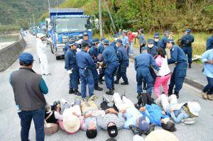 ダンプカーによる石材運搬を阻止しようと路上に寝転がり、機動隊員に排除される市民=13日午前9時すぎ、国頭村・奥港