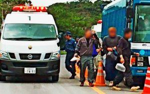 警察車両(左)から降り、米軍北部訓練場に入る作業員ら=2日午後0時ごろ、東村高江のN1ゲート(読者提供、画像の一部を加工しています)