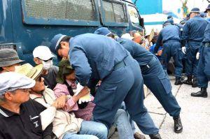 座り込み抗議する市民を強制排除する機動隊員ら=27日午前、名護市辺野古キャンプ・シュワブゲート前