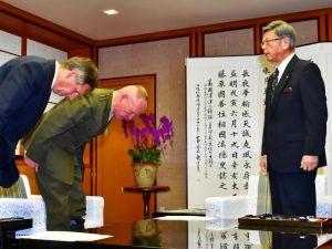翁長雄志知事(右)に頭を下げて謝罪するニコルソン四軍調整官(左から2人目)ら=20日午後3時半、沖縄県庁