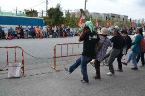 キャンプ・シュワブゲート前で、道の両端に並んで腕を組み、「上を向いて歩こう」に合わせて歌い踊る市民ら=4日午前11時すぎ、名護市辺野古