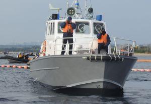 フロート沿いを警備するマリンセキュリティーの警備艇=2016年4月、名護市辺野古の米軍キャンプ・シュワブ沖