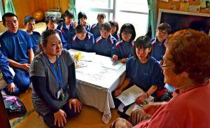 新垣ハルさん(右)から、宮森小のジェット機墜落当時の話を聞く伊波中の生徒ら=5月2日、読谷村内