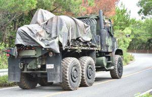 ヘリの残骸を載せ、県道70号を北上する米軍の大型トラック=20日午前10時21分、東村高江