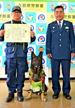 与那原署長賞を受賞した警察犬のガンタ号とパートナーの宮平守巡査長(左)、仲地隆穂署長=27日、与那原署
