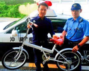 発見した沖縄署員から、自転車を受け取った末広尚希さん(左)=10月2日、宜野湾市