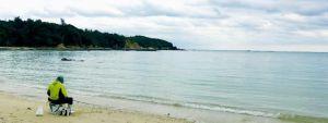 海岸から墜落現場を望む砂浜。釣り人が糸を垂らしていた=12日午前11時すぎ、名護市安部