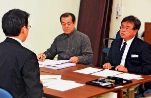 防衛局の遠藤次長(左)に抗議する名護市の山里副市長(右)=5日、名護市役所