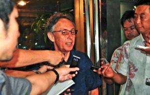 支援者との会合を終え、記者団の質問に応じる玉城デニー衆院議員(中央)=21日、沖縄市