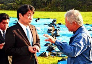 米軍ヘリ炎上事故の現場で被害者の西銘晃さん(右)から話を聞く小野寺五典防衛相=25日午前、東村高江