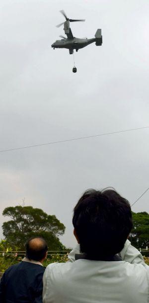村職員らが見上げる中、物資をつり下げて旋回するオスプレイ=6日午後3時47分ごろ、宜野座村城原区内