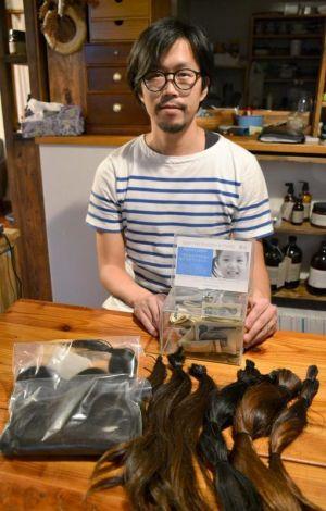 胸まであった髪を切って寄付した川名さん。客から寄付された髪やお金はまとまってからJHDACへ送るという=読谷村座喜味・hair room botanika