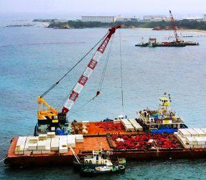 米軍普天間飛行場の移設に向けた海上の本体工事が始まり、沖縄県名護市辺野古沿岸部では海中に設置する大型コンクリート製ブロックを台船(手前)からクレーン船に移す作業が行われた。奥は米軍キャンプ・シュワブ=6日午後(小型無人機から)