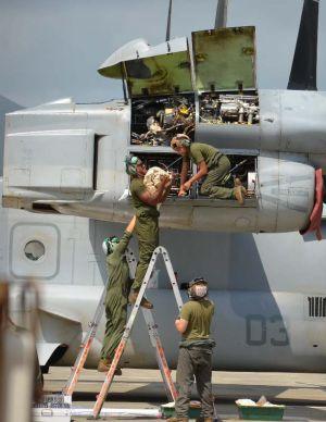オイル漏れのあった機体の右翼エンジンから部品を抜き取り、地面に運び出す米兵=1日午前11時50分、新石垣空港
