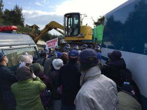 新基地建設に反対する市民らの横を通り、米軍キャンプ・シュワブ内に入る工事車両=27日午前、名護市辺野古