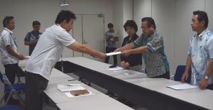 沖縄防衛局企画部の池田眞人次長(左)に、米軍のパラシュート降下訓練に対する抗議文を手渡す社大党の大城一馬委員長(右から2人目)ら=24日、沖縄防衛局