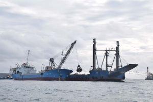クレーンを使って待機していた台船に石材を積み替える作業船=10日午前9時13分、名護市辺野古