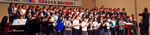ステージで熱唱する保護者や教職員、地元住民ら=宜野湾市民会館(同中PTA提供)