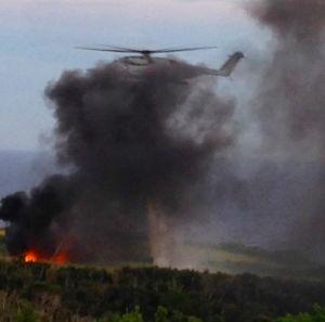 墜落直後の現場。黒煙をあげている米軍機「CH53E」(左下)の消火活動にあたるヘリ(中央)=11日午後6時9分、東村高江(西銘美恵子さん提供)