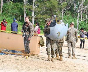 オスプレイの機体の破片を運ぶ米兵=15日午前10時40分ごろ、名護市安部(浦崎直己撮影)