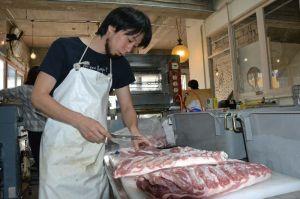仕入れた豚肉を部位ごとに仕分するソーセージ職人の嶺井大地さん=19日、沖縄市中央