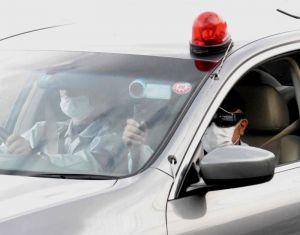沿道で抗議する市民にビデオカメラを向ける警察官=9日午前8時すぎ、大宜味村喜如嘉