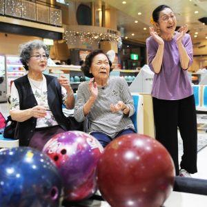 笑顔でボウリングを楽しむ(左から)宮里美子さん、長田光子さん、山里史さん=16日、那覇市・サラダボウル(崎浜秀也撮影)