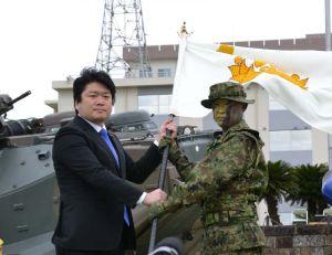 山本朋広防衛副大臣(左)が青木伸一水陸機動団長に団旗を授与した=7日、長崎県佐世保市の相浦駐屯地