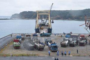 台船に石材を積み込むダンプカー=13日午後1時27分、国頭村・奥港
