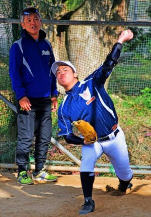 今年の初練習で投げ込みする田場一志さん(右)と指導に当たる藤井智監督=4日、西原高校グラウンド