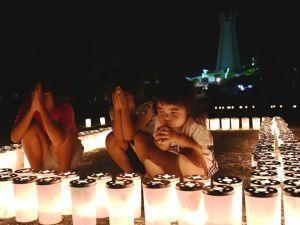 平和祈念公園内にともされたろうそくに手を合わせる子どもたち=22日午後8時すぎ、糸満市摩文仁(渡邊奈々撮影)
