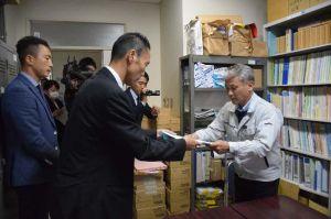 沖縄防衛局の阿野貴史次長(左)から特別採捕許可の申請書を受け取る県水産課の平安名盛正課長=24日、県庁