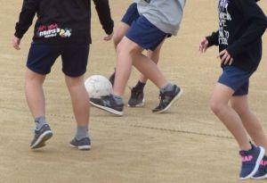 55日ぶりに使用が再開された運動場でサッカーをする児童たち=6日午前10時すぎ、宜野湾市・普天間第二小学校