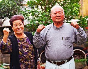 ガッツポーズする當山誠篤さん(右)と富美さん夫妻=15日、宜野湾市喜友名の自宅
